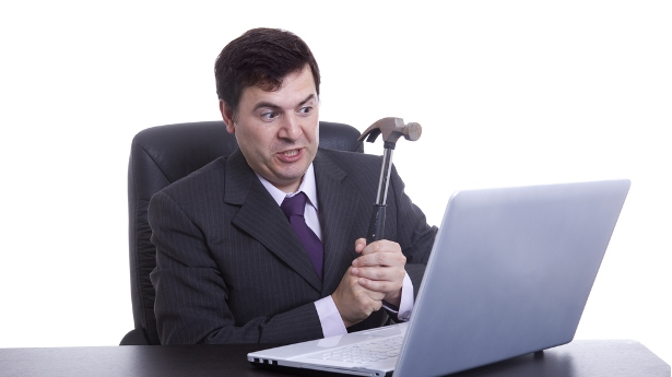 A business man considers smashing his computer. Photo: Shutterstock.com, all rights reserved.
