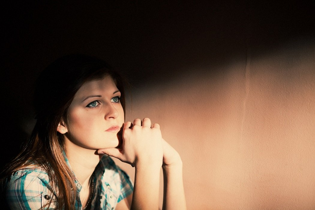 Young woman suffering from a severe depression in a line of light