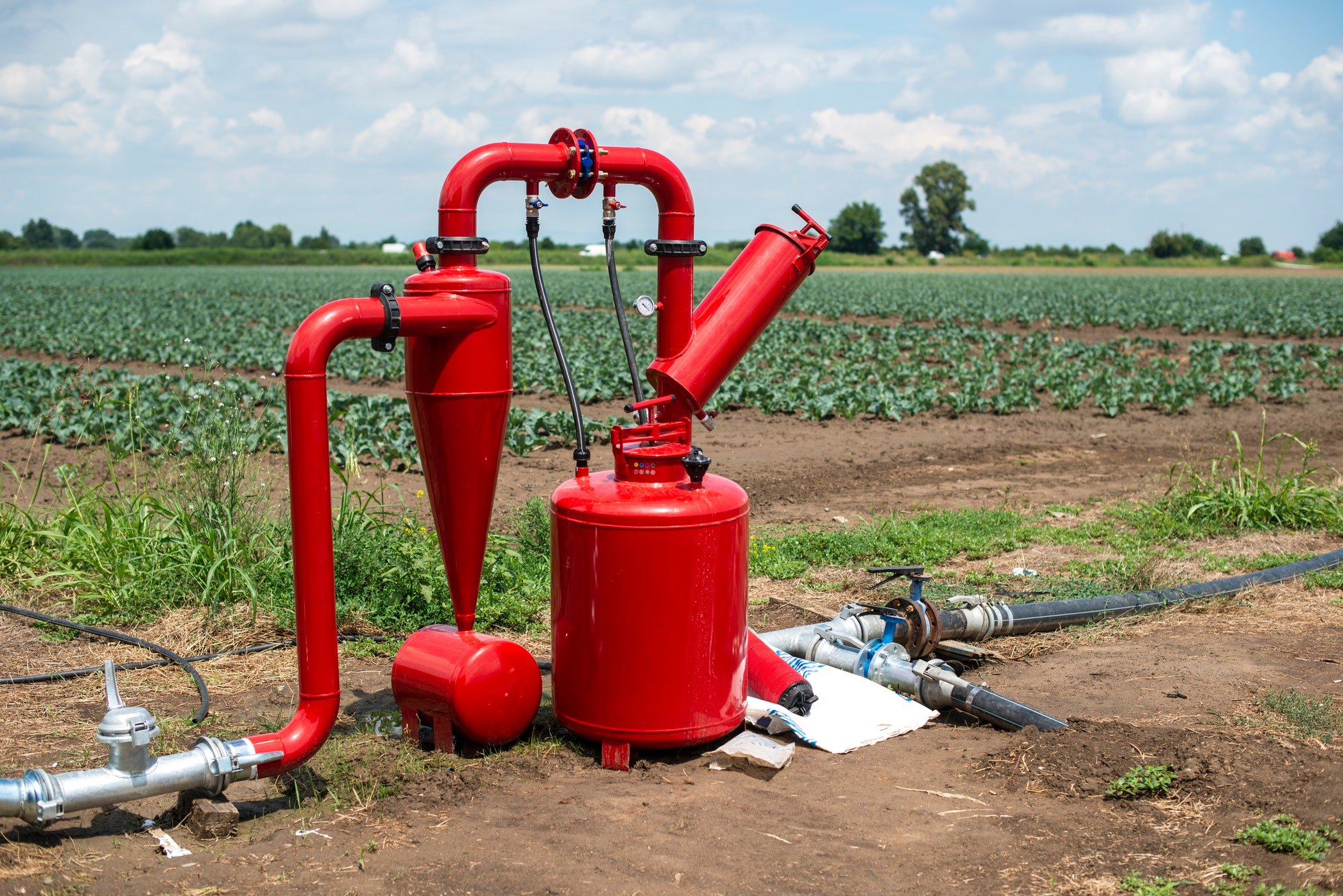 Water pump and pipes on farmland.