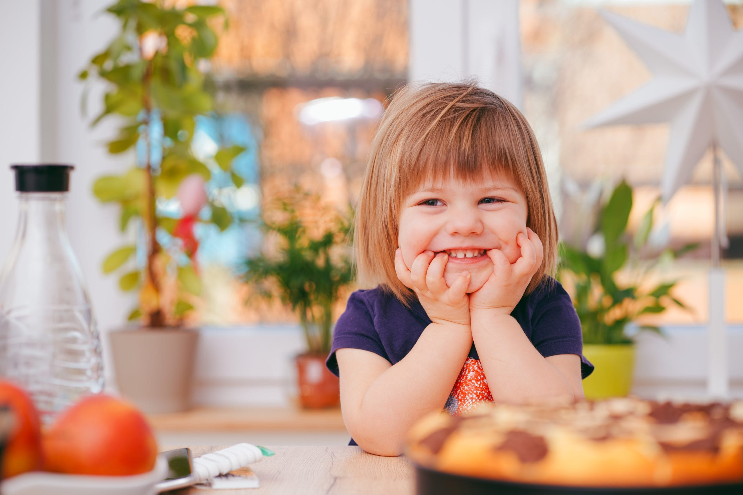 Toddler Grinning while Sitting on a Dining Table