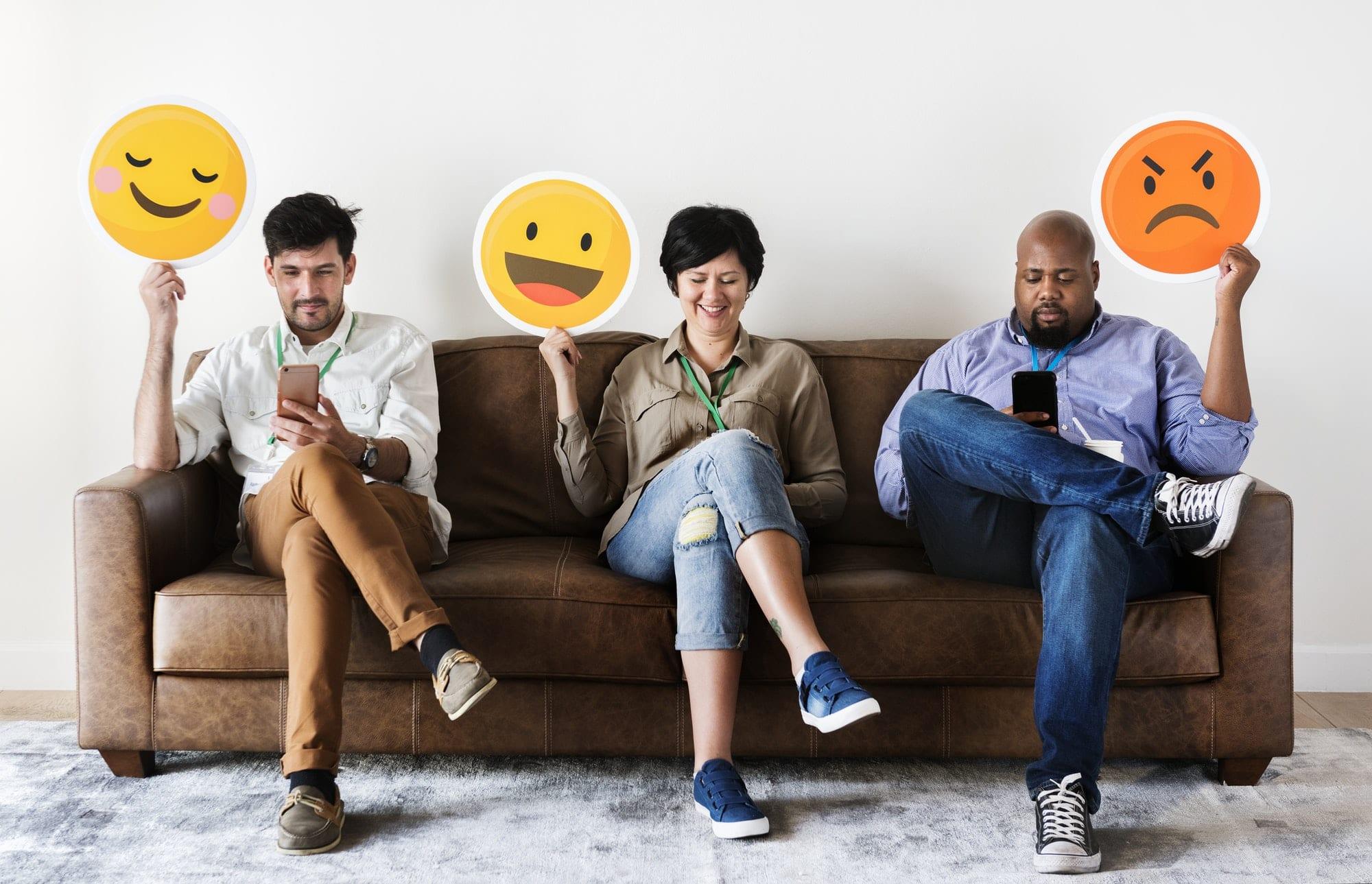 Diverse people sitting and holding emojis logos