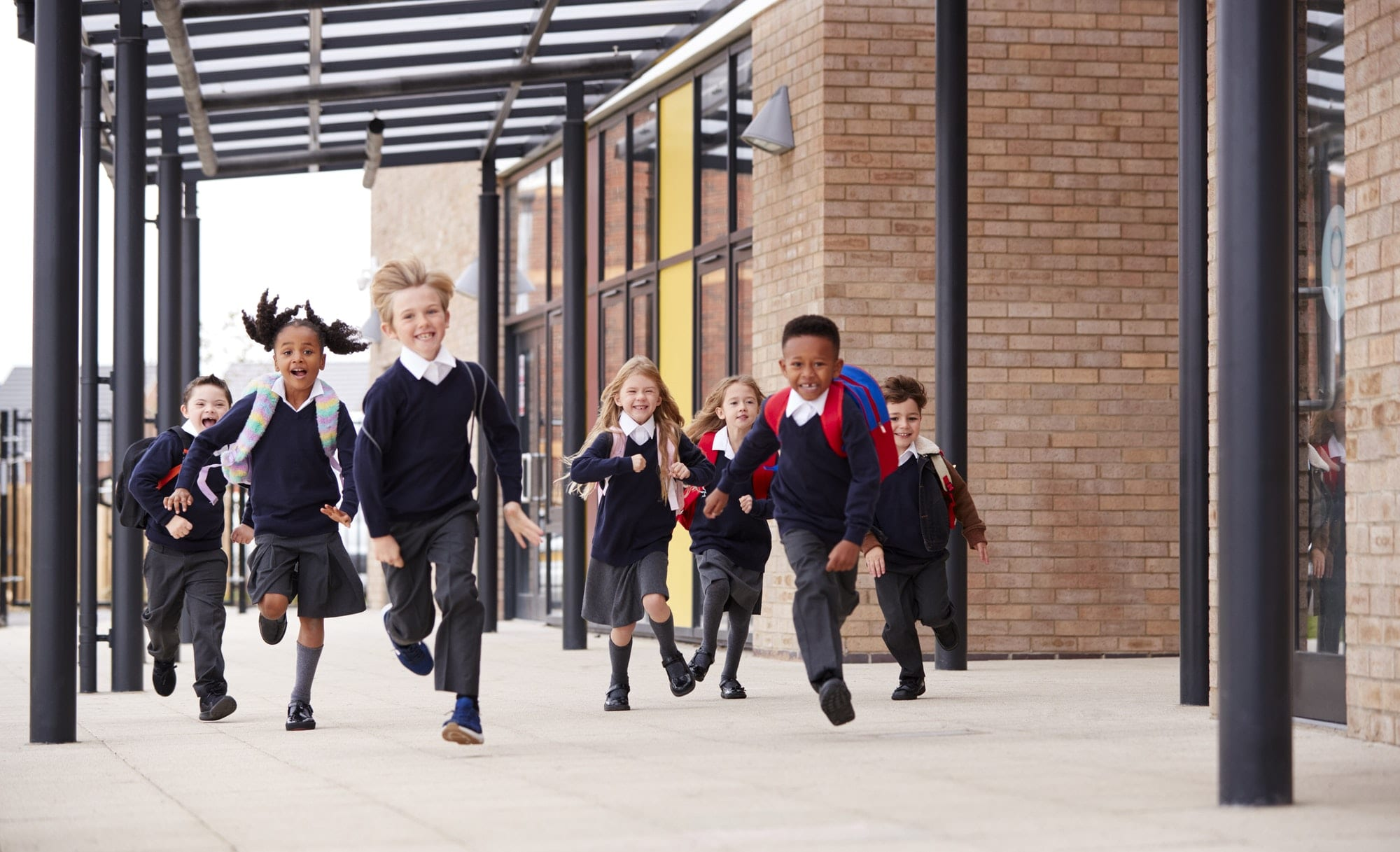 Primary school kids, wearing school uniforms and backpacks, running on a walkway