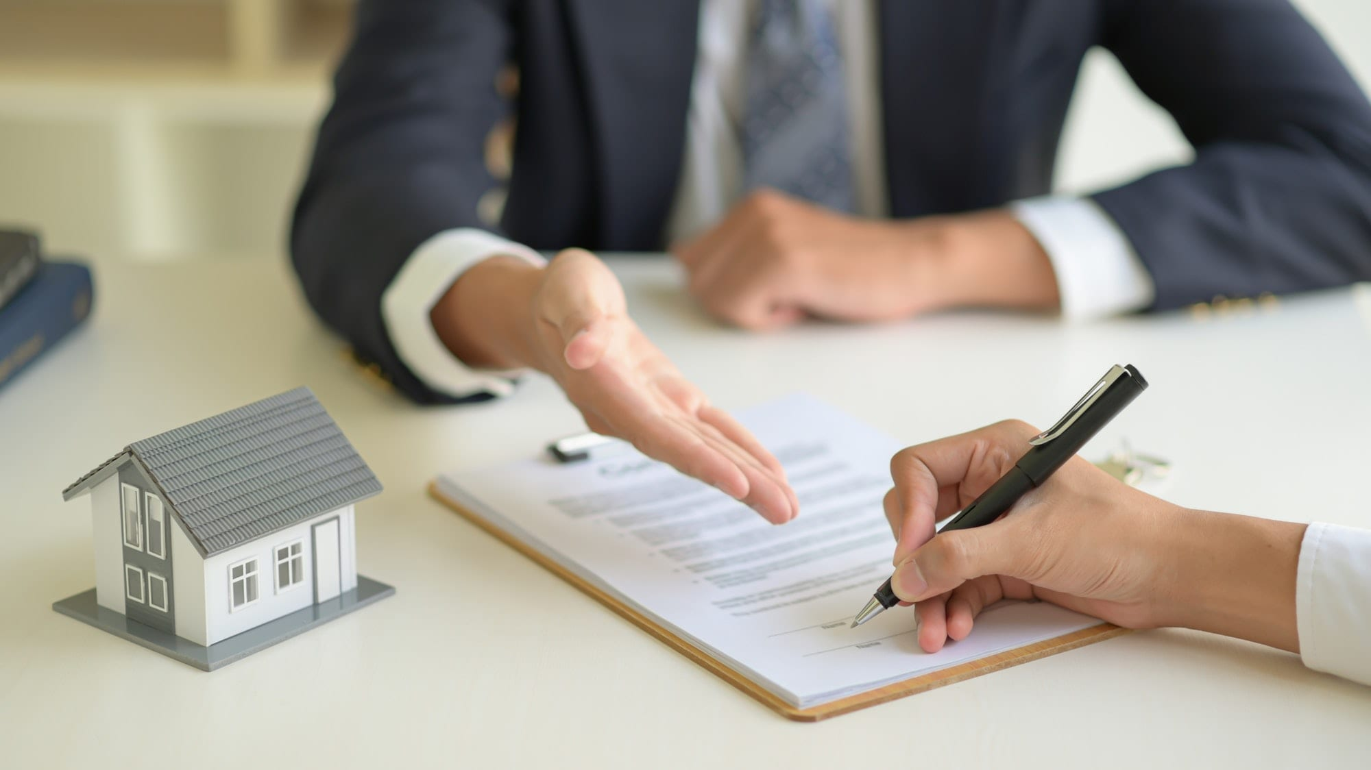 Signing a home purchase contract between the house broker and the client.