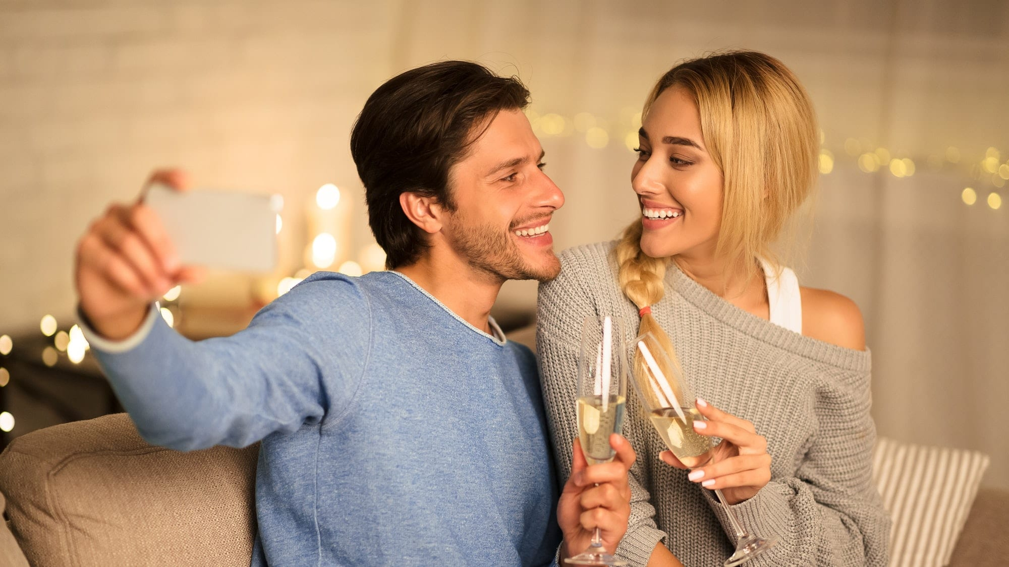 Young couple celebrating anniversary with champagne at home