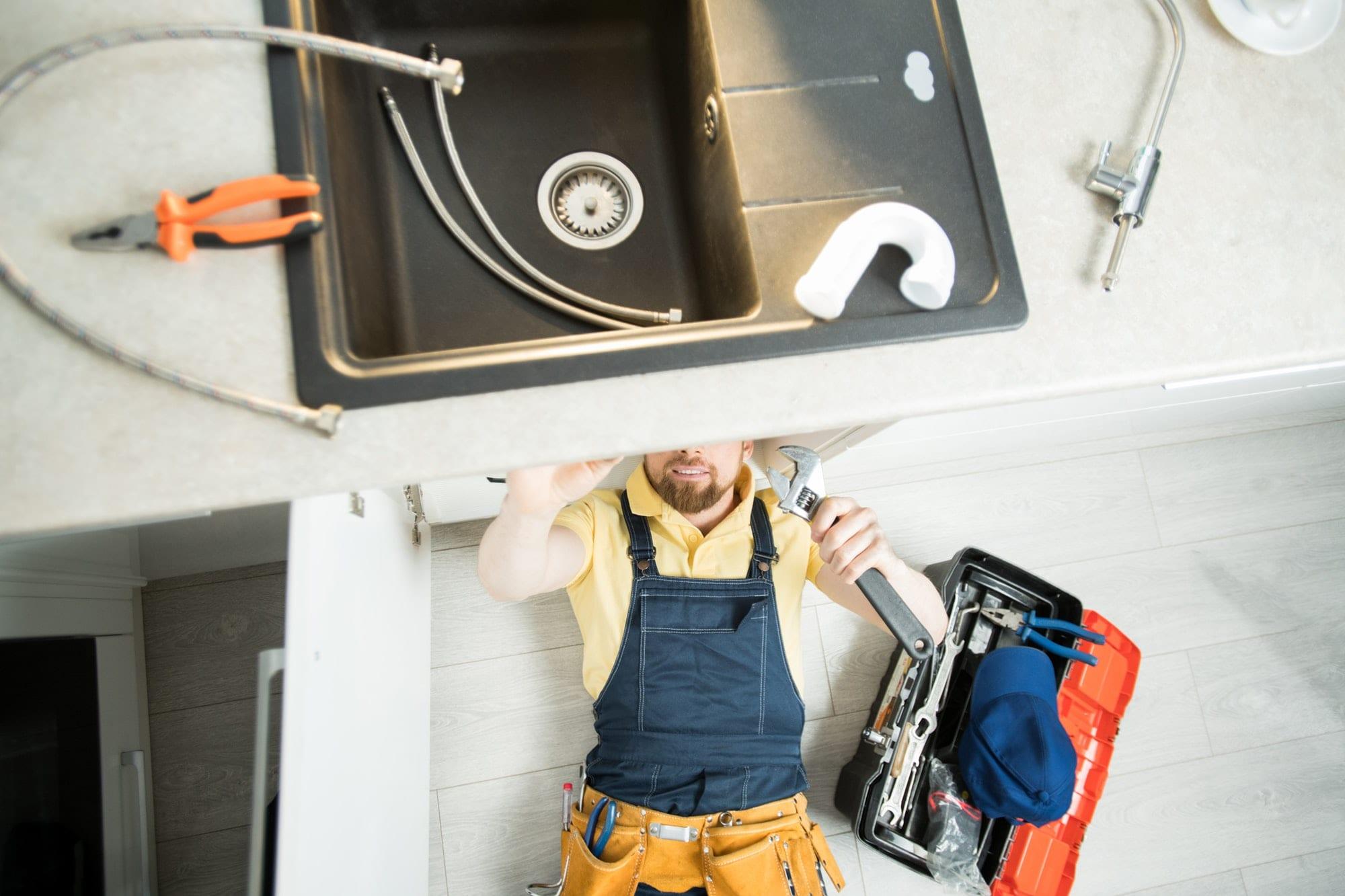 Plumber repairing pipe in kitchen