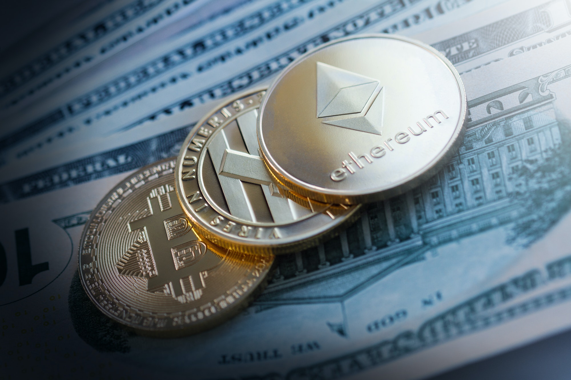 golden cryptocurrency coins on dollar bills