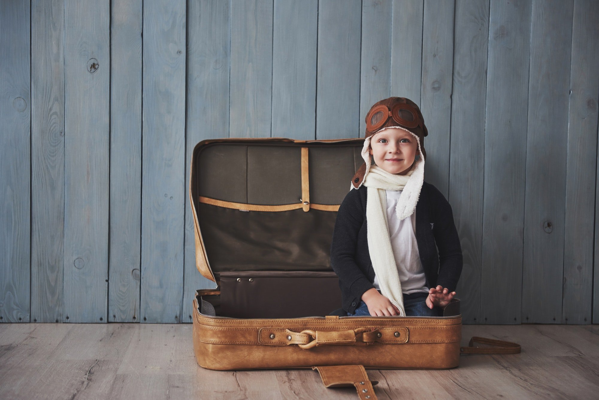 Happy kid in pilot hat playing with old suitcase. Childhood. Fantasy, imagination. Holiday