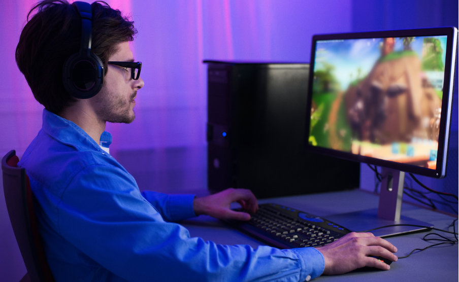 Man with dark hair and glasses playing games on a PC