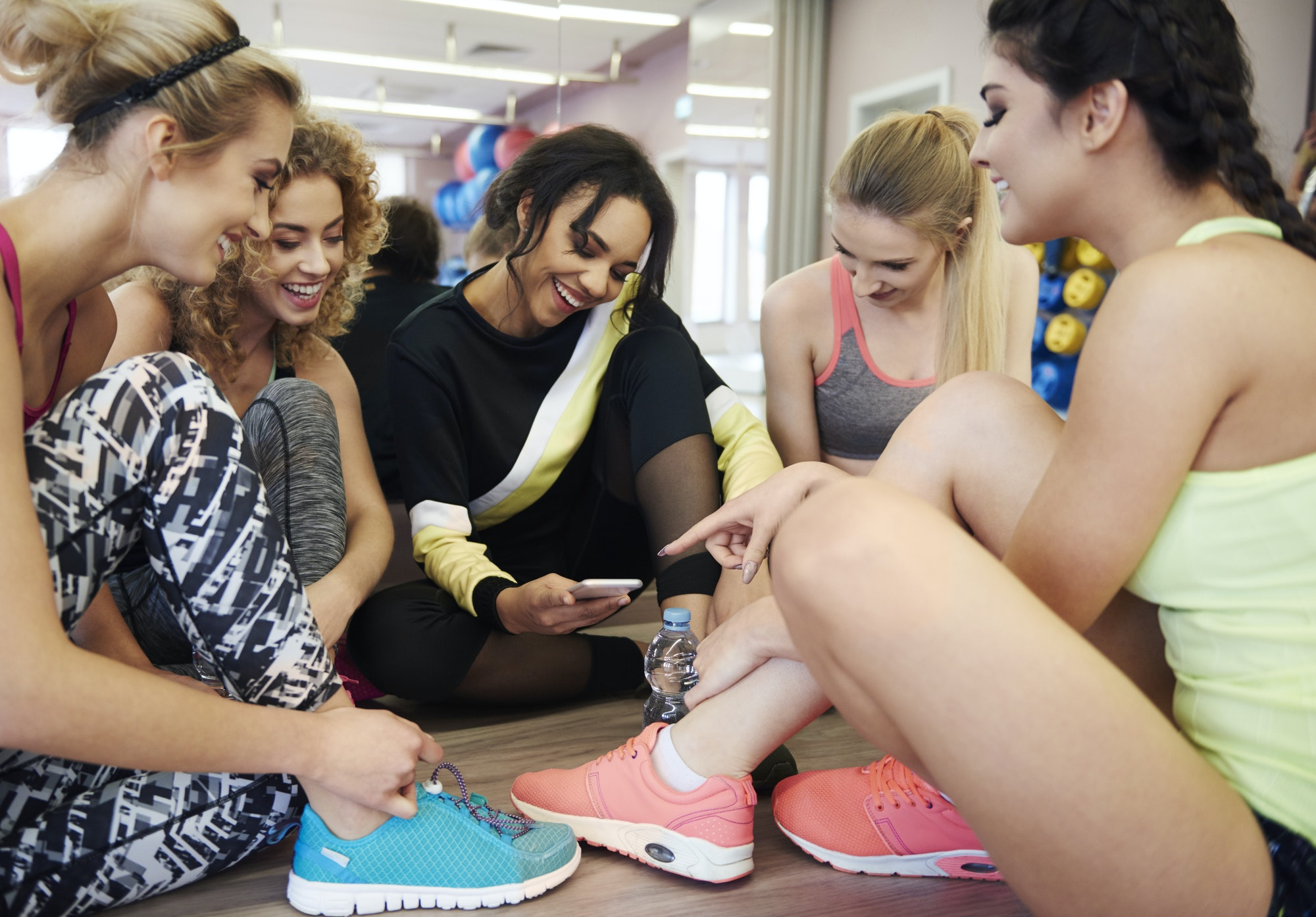 Girls checking news on the phone in fitness apps