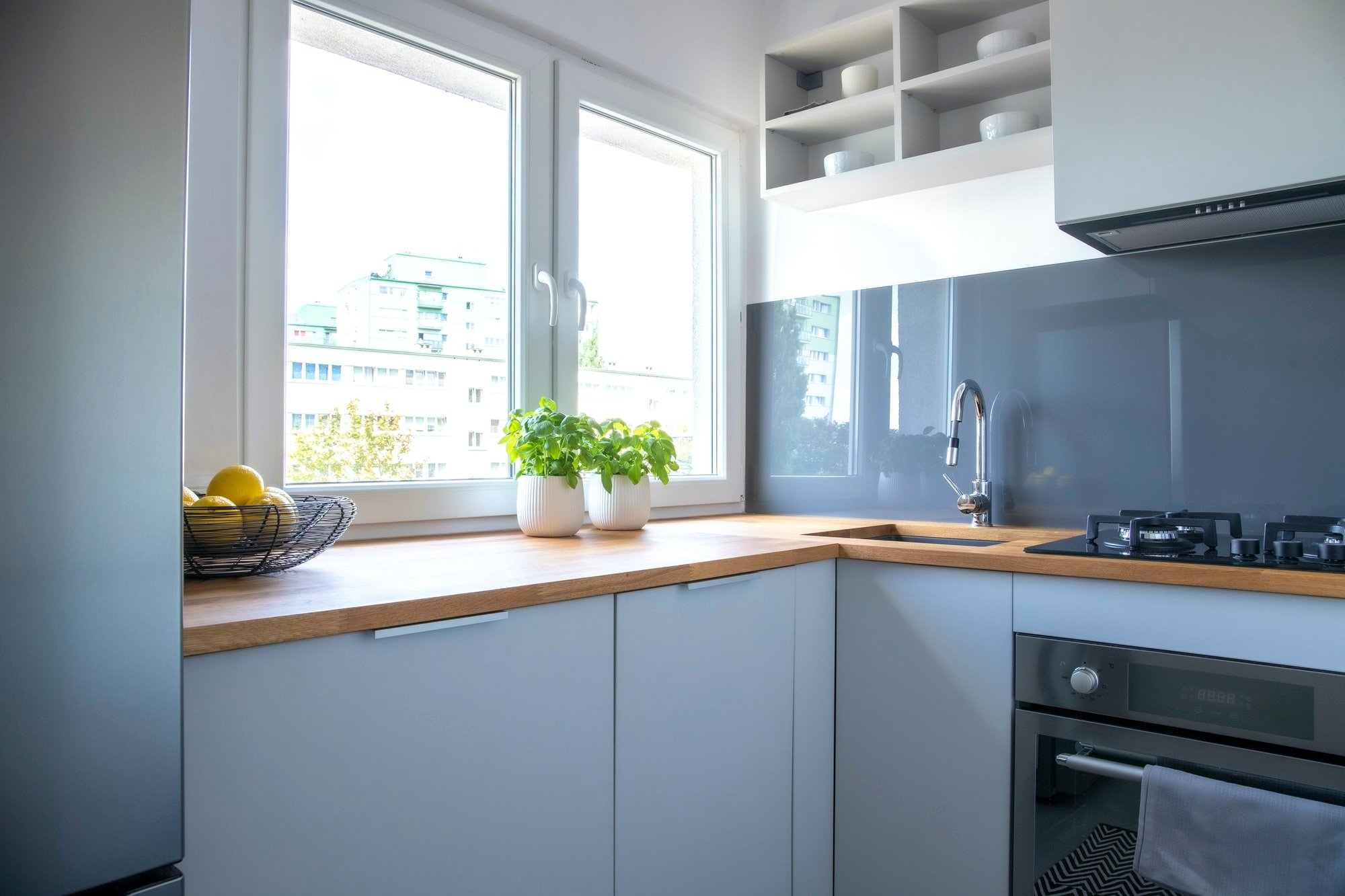 Herbs and lemons on wooden counter of small kitchen with white cupboards