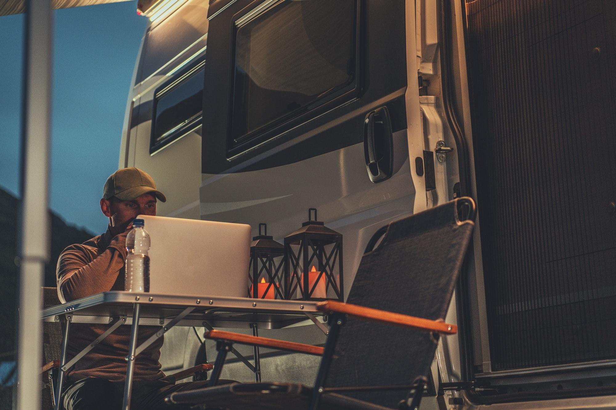 Self Employed Men Doing His Online Job Next to Camper Van