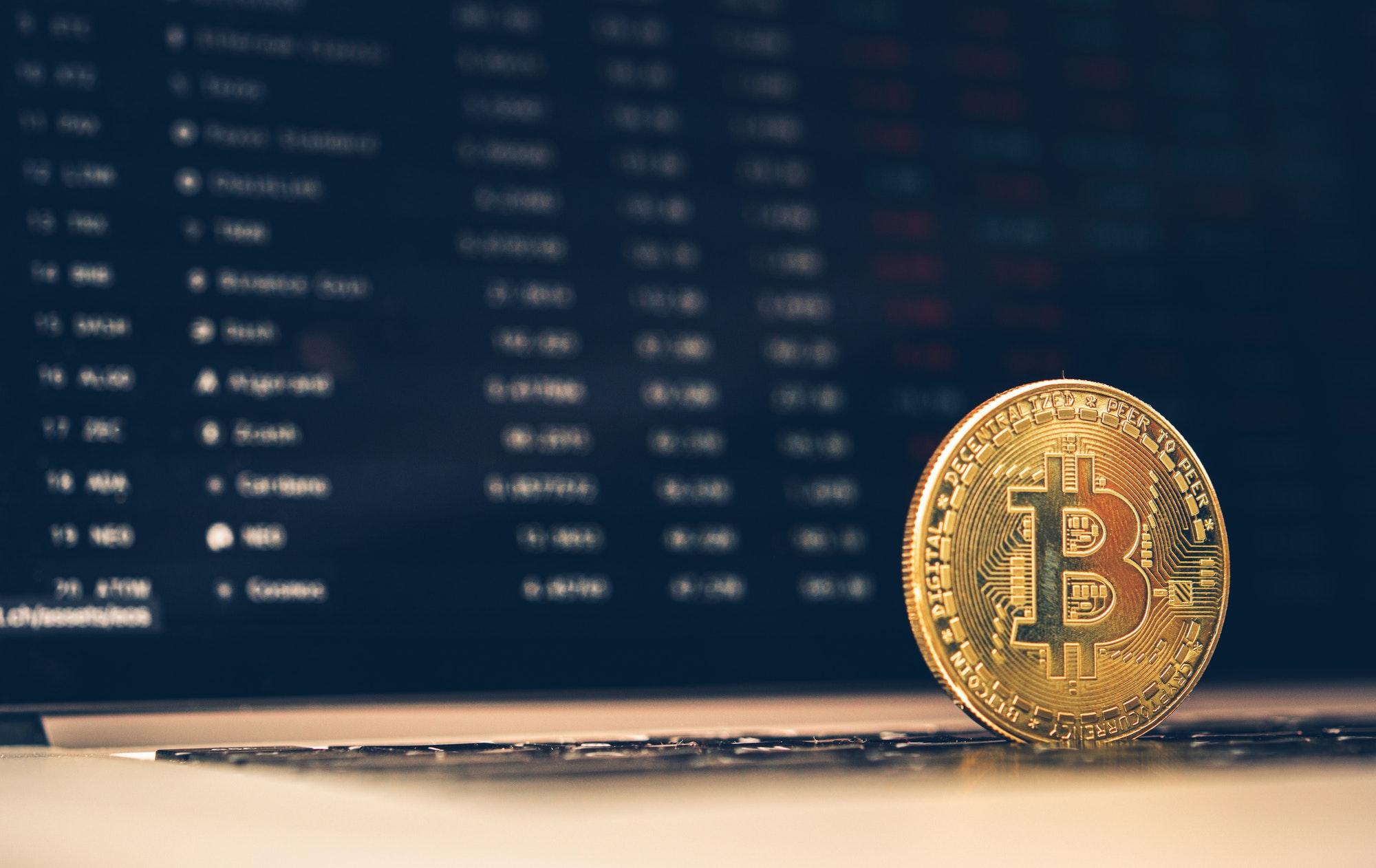 Golden Bitcoin Metal Symbolic Coin on Computer Keyboard