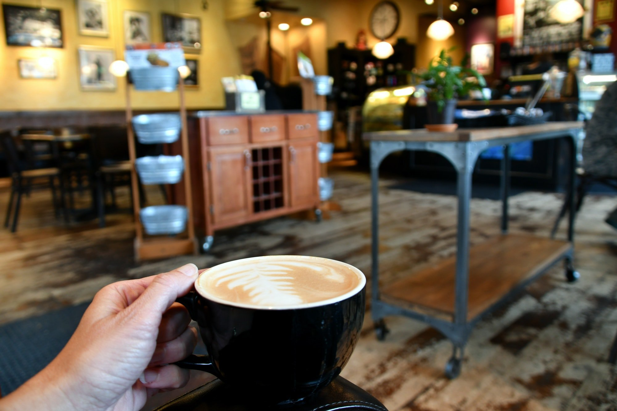 Relaxing in a colorful local business coffee shop with a hot coffee latte - real people