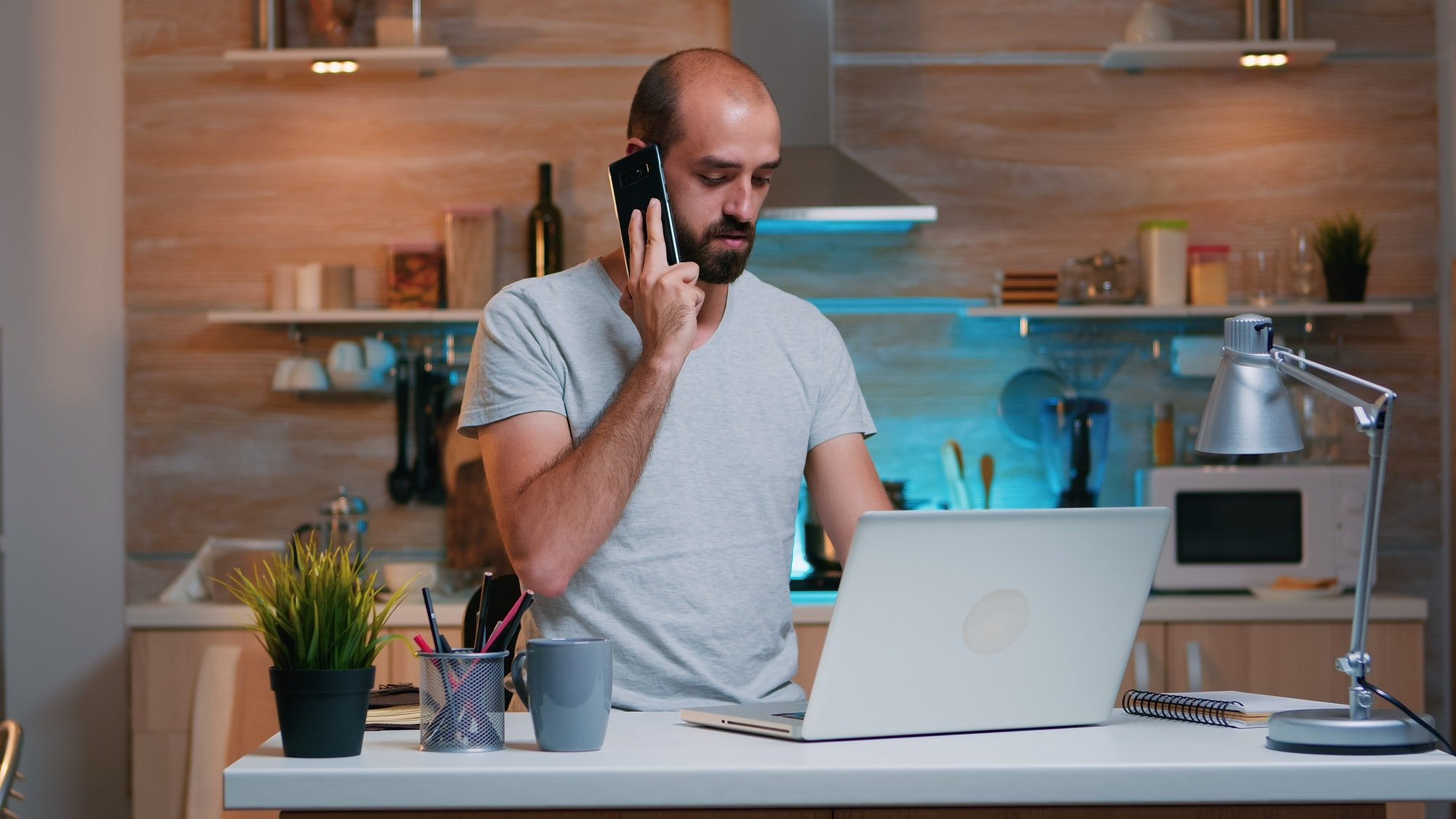 Remote worker typing on pc and speaking at phone