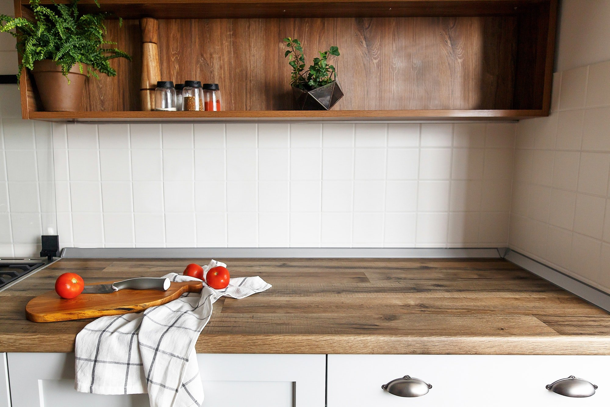 Wooden board with knife, tomatoes, towel on modern kitchen countertop