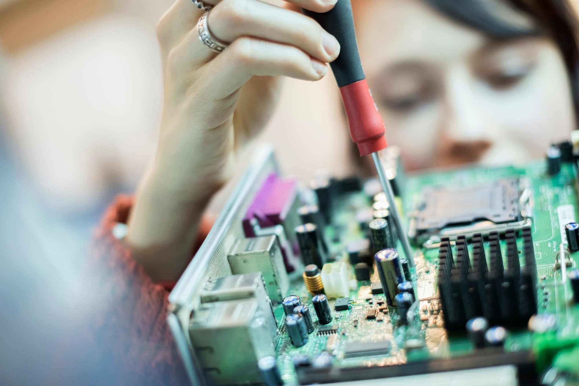 A woman using an electronic screwdriver on a computer circuitboard.
