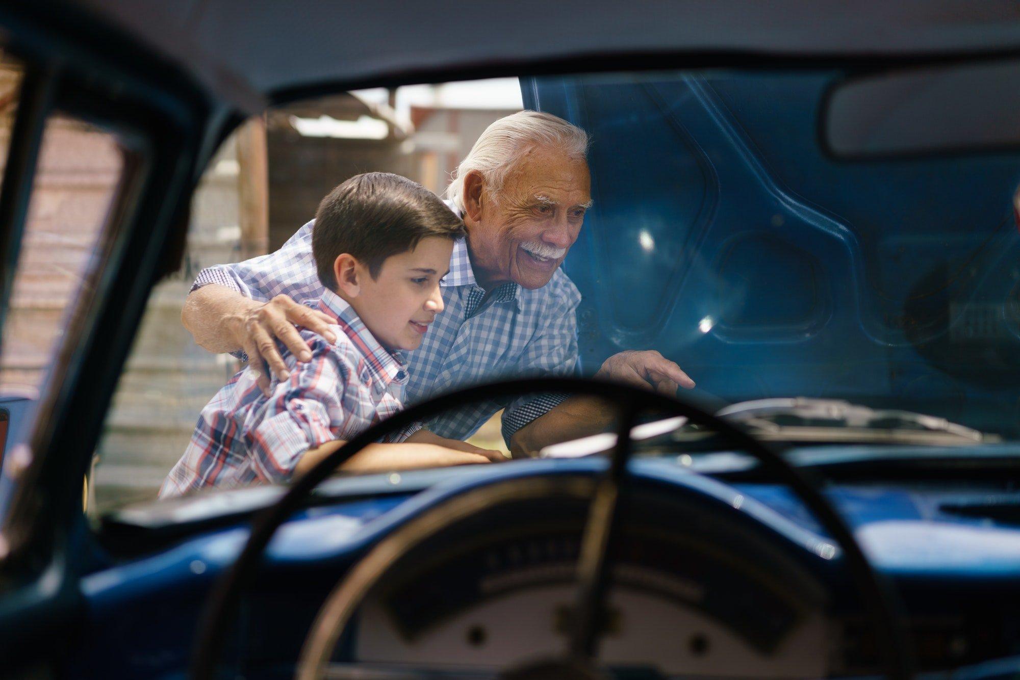 Boy With Grandpa Looking Car Engine Of Senior Man