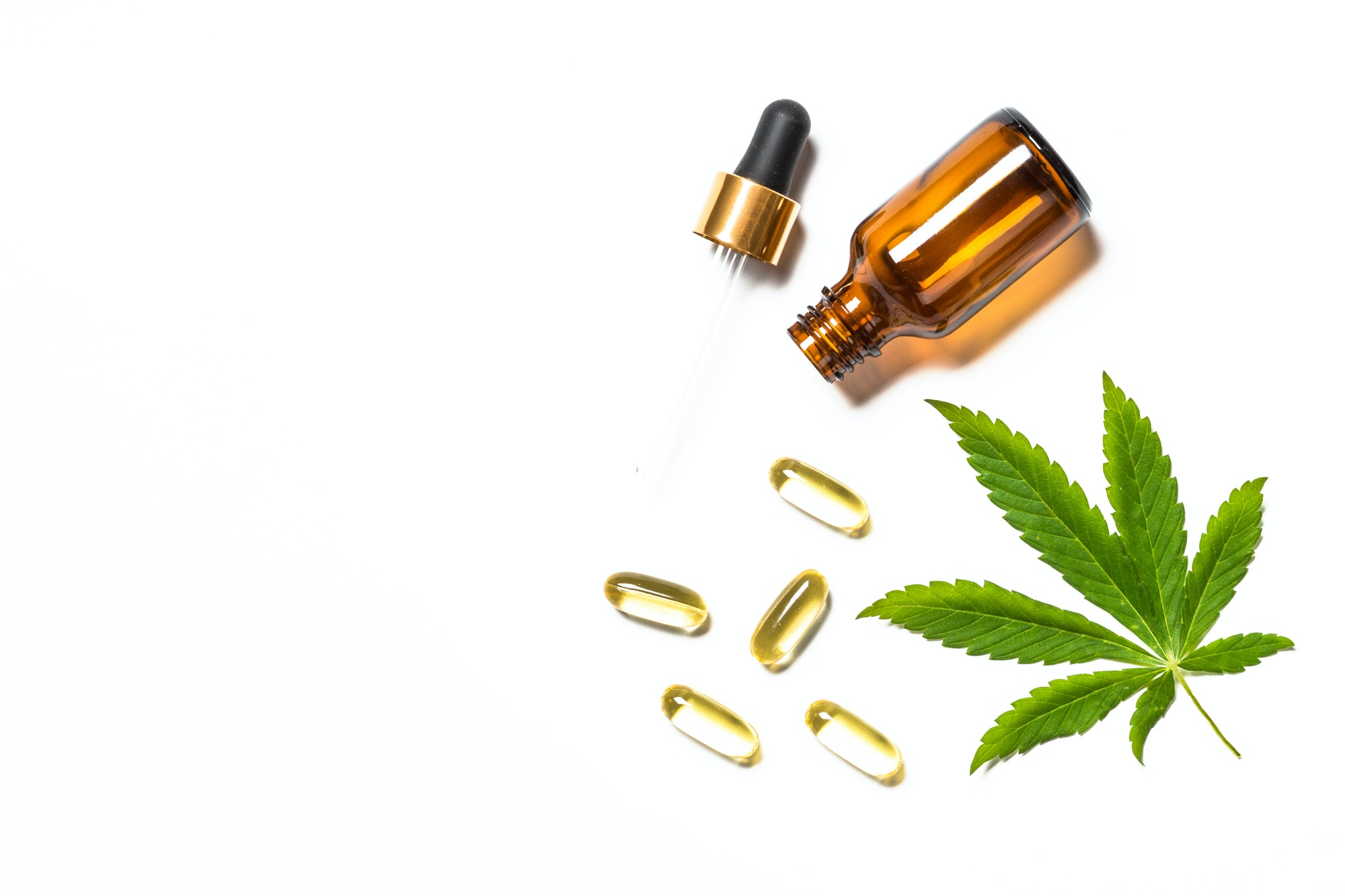 Cannabis oil, pills and green leaves at white table