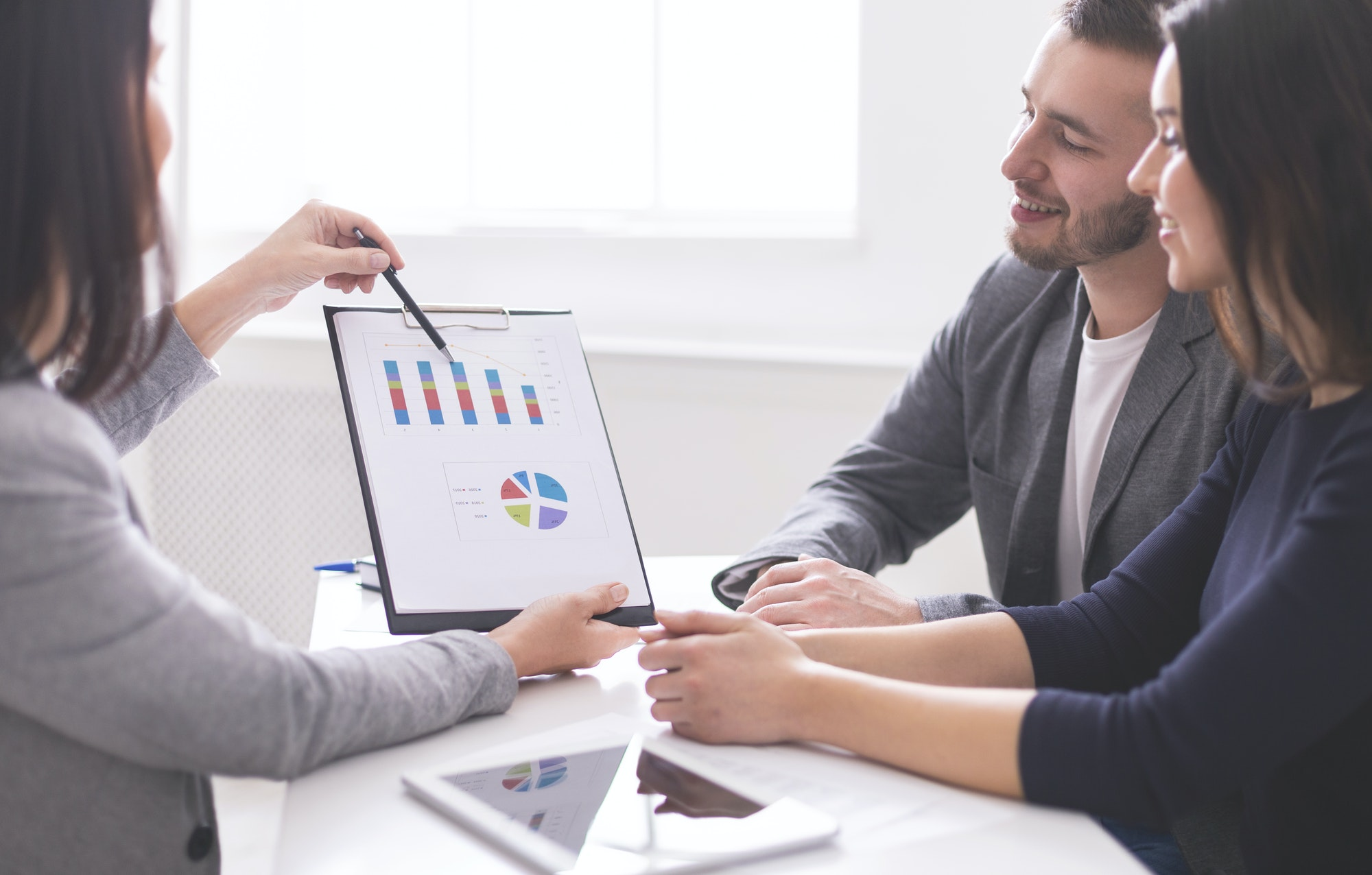 Financial advisor showing payments plan to young couple