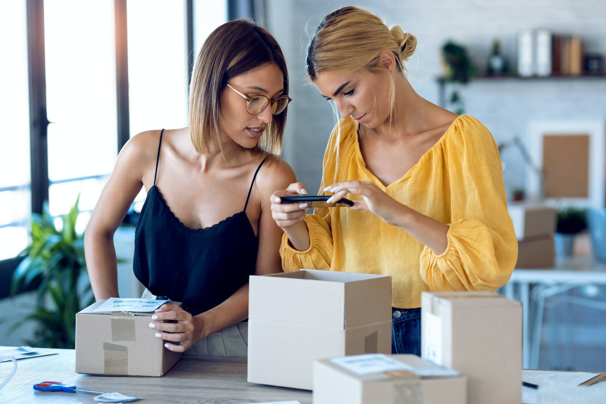 Two beautiful freelance business women using smart phone to taking photos to sell online