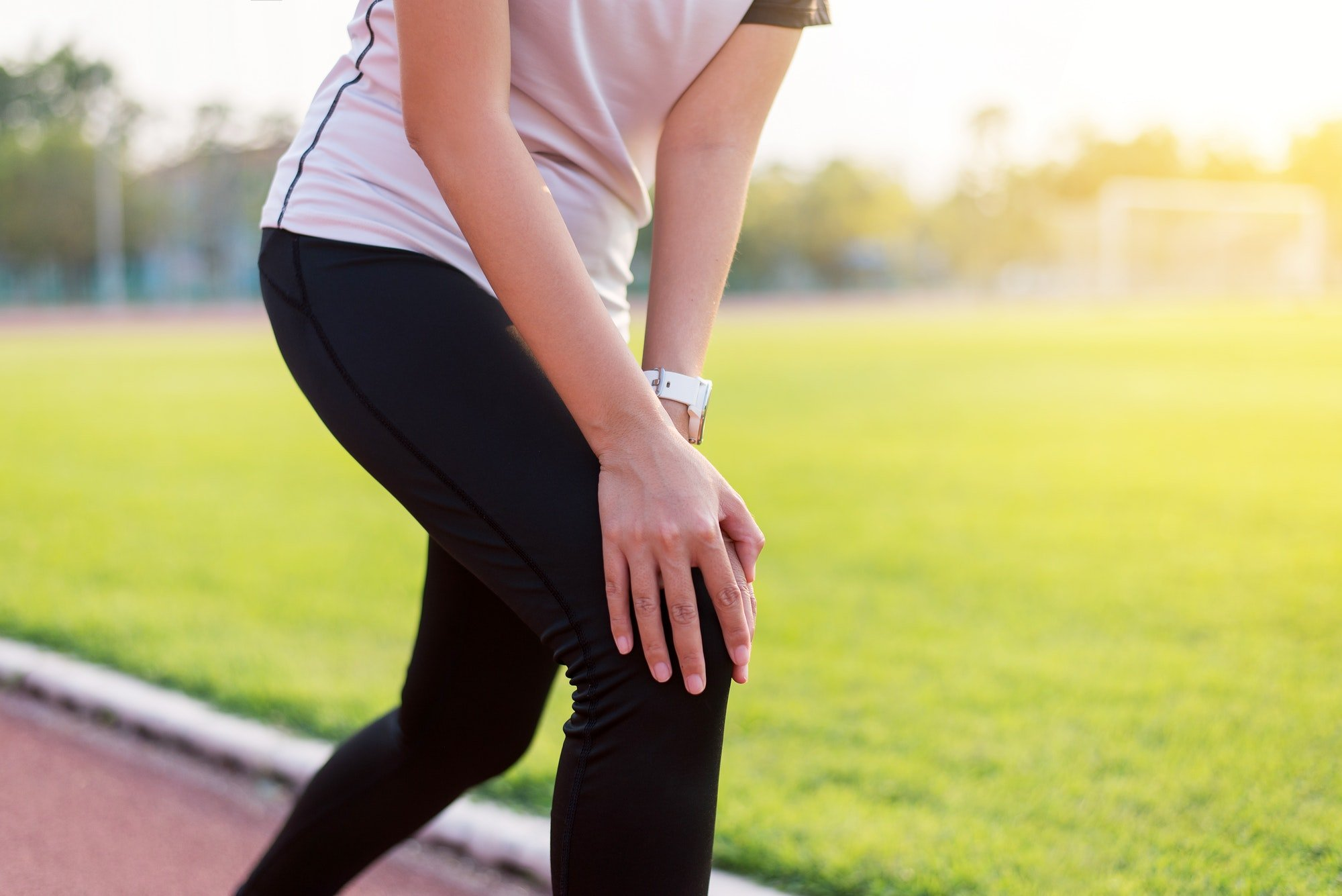 Beautiful women runner having a knee pain and injury after running