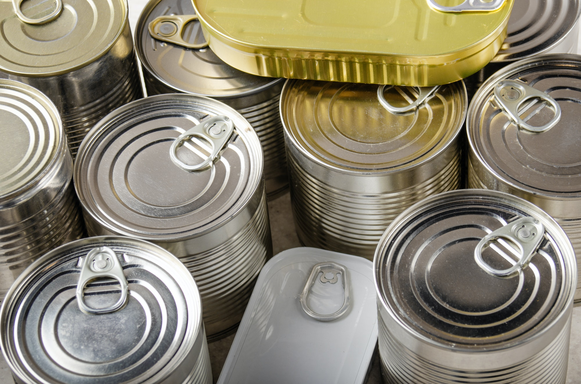 canned foods in tin cans on kitchen table
