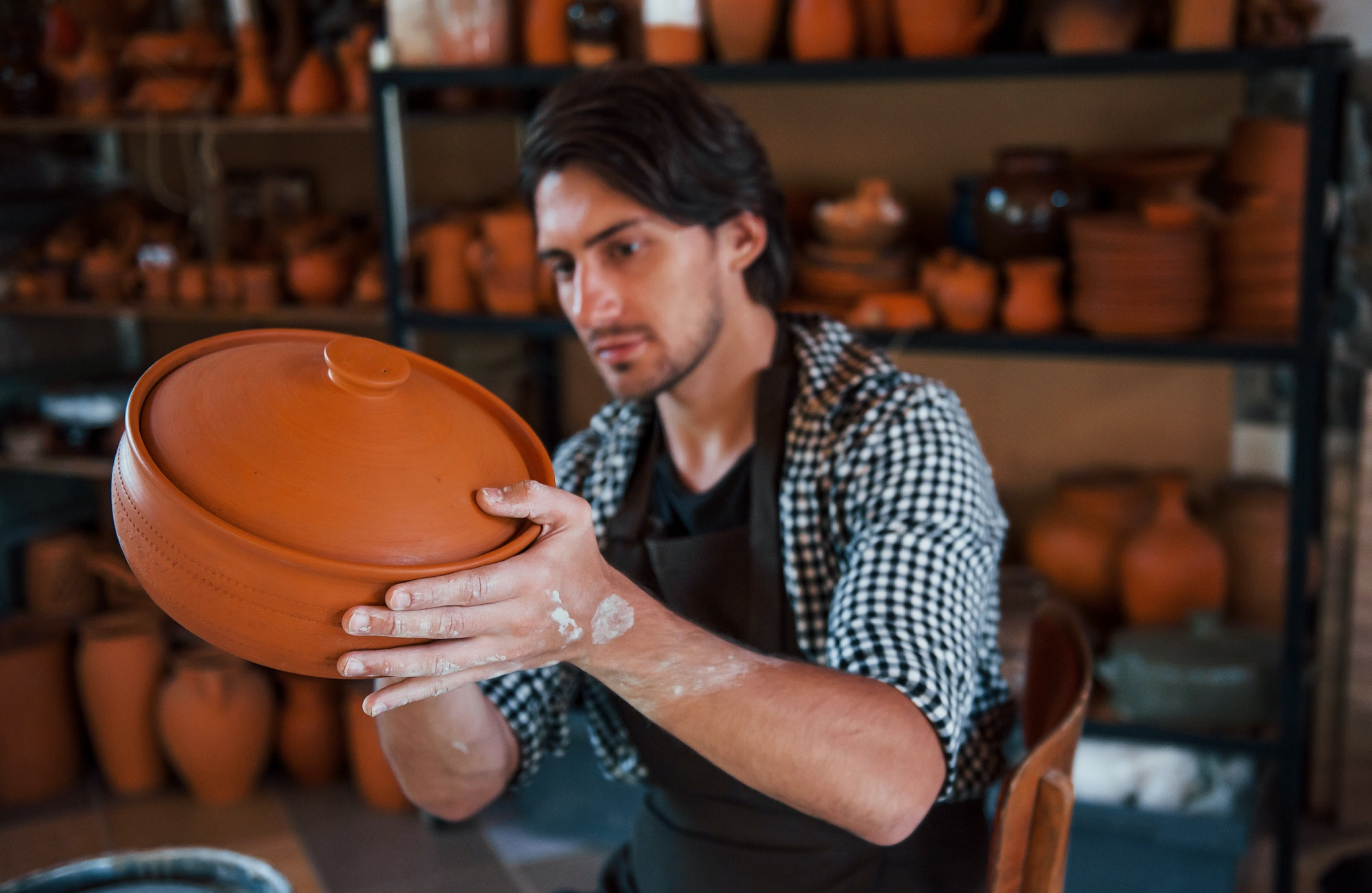 Young ceramist holds fresh handmade product made of clay in hands and looks at results of his work