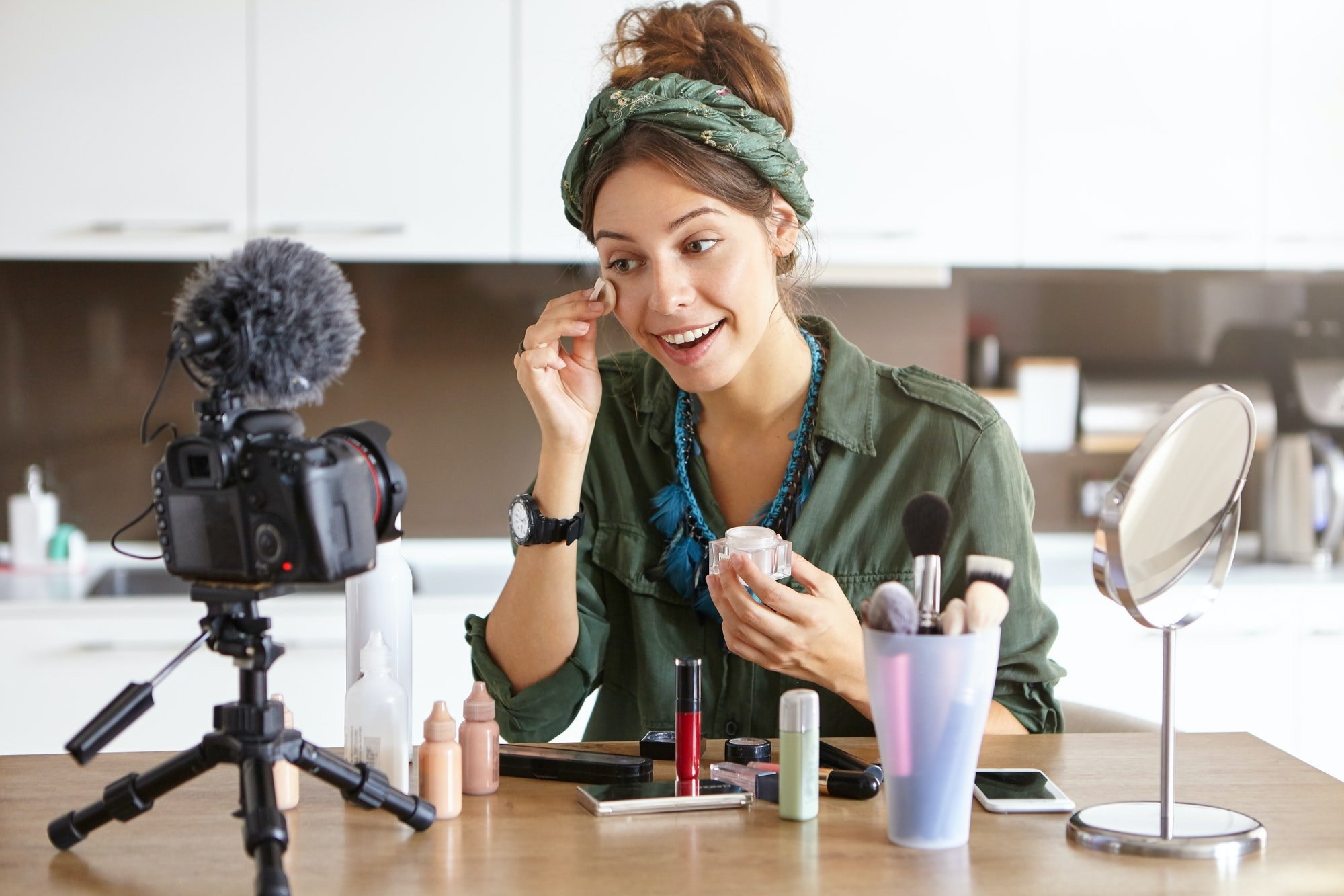Attractive young woman beauty fashion blogger using sponge while applying powder, talking about cosm