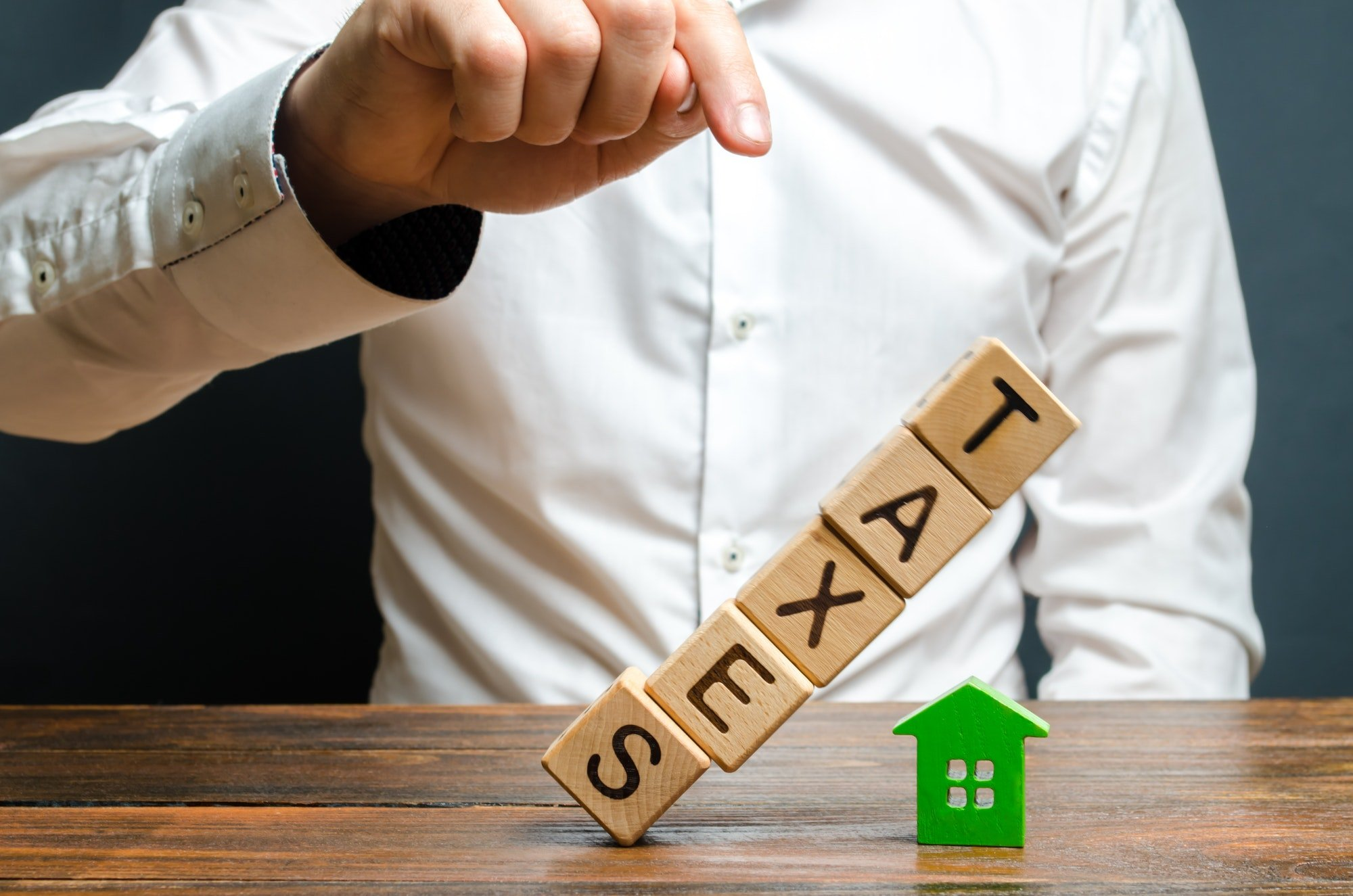 The man pushes down the tower of cubes with the word Taxes on the figure of the house