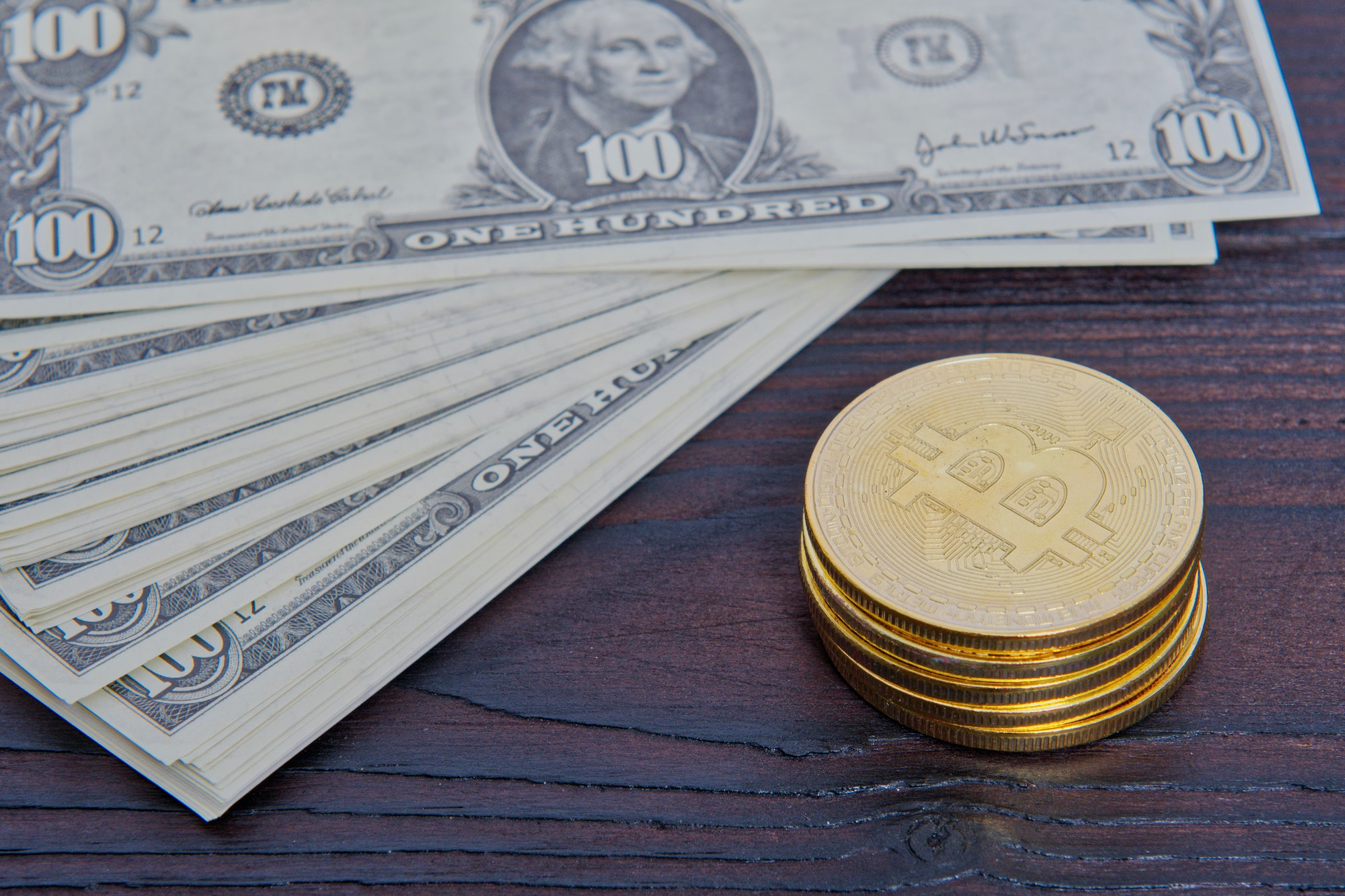 Dollar banknotes and Bitcoins on a table